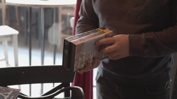 Man buying vintage video cassettes with movies on vhs from a thrift shop