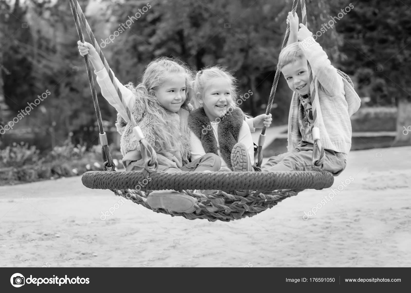 Tre Bambini Che Giocano Nel Parco Con Swing Bianco Nero Foto Stock