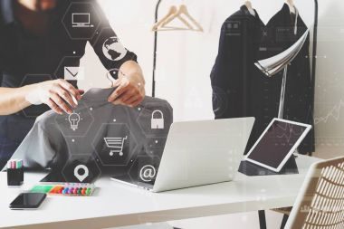 Fashion designer holding shirt and using laptop with digital tab