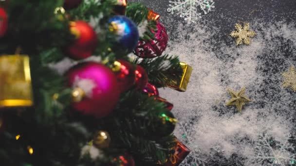Pozdravem sezóny koncept. Gimbal záběr ozdoby na velký vánoční stromek s dekorativní světlo a padající sníh v rozlišení 4k (Uhd)