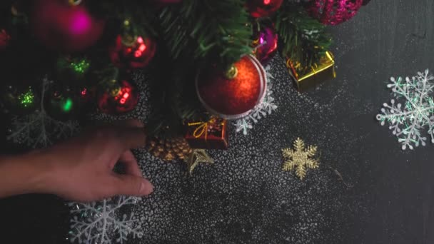 Greeting Season concept. Hand setting Christmas tree and decorations with presents and ornaments on white wood table from above with falling snow in 4k (UHD)