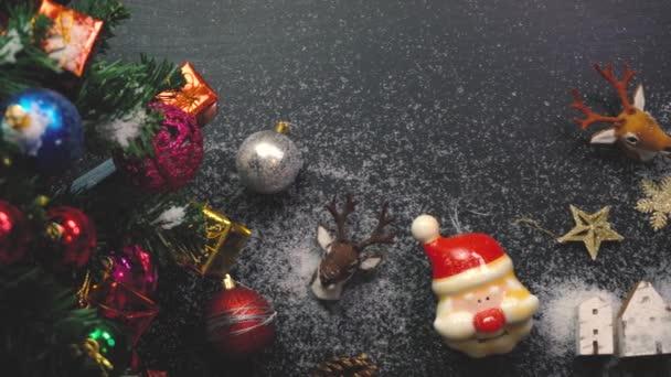 Pozdravem sezóny koncept. Ruční nastavení vánoční stromek a ozdoby s dárky a ozdoby na bílé dřevo stůl z výšky s padajícím sněhem v rozlišení 4k (Uhd)