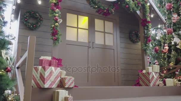 Pozdravem sezóny koncept. Prstenec záběr ozdoby na vánoční stromeček s dekorativní světlo a přední s dveřmi v rozlišení 4k (Uhd domů)