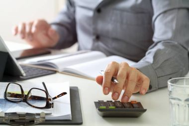 businessman hand working with finances about cost and calculator