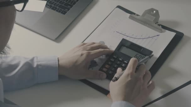 Above view of Healthcare costs and fees concept.Hand of smart doctor used a calculator for medical costs in modern hospital in slow motion