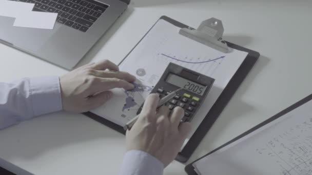 Podnikatel ruka spolupracujícímu s financemi o nákladech a Kalkulačka a notebook s mobilním telefonem na stůl v moderní kanceláři