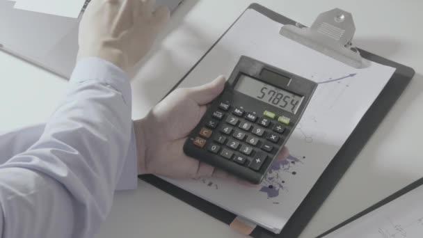 Podnikatel ruční práce s financemi o náklady a kalkulačka a notebook s mobilním telefonem na stole v moderní kanceláři