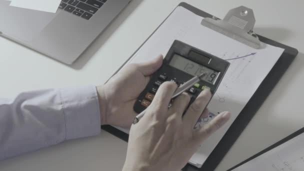 Üzletember kézzel dolgozik a pénzügyek, a költség és a számológép és a laptop-val mozgatható telefon a modern irodai íróasztal