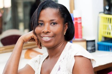 This beautiful smiling woman sitting at the hair salon looking at the camera.