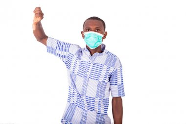 a young man in a blue t-shirt standing on a white background wearing a medical mask and with his thumb raised up.