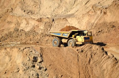 Big yellow dump truck transporting sand in an open-pit mining quarry. Mining quarry for the production of crushed stone, sand and gravel for use in the construction industry - image