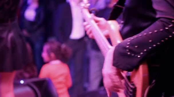 Férfiak basszusgitározni a színpadon.