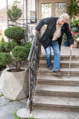 Ederly man with a cane descends down the stairs outdoors