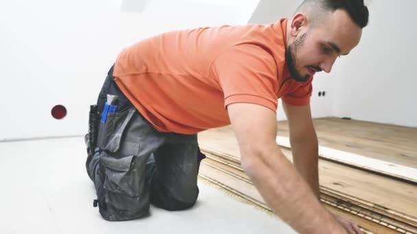 mužský dělník instalující parketovou podlahu na staveniště. Položit parketovou podlahu