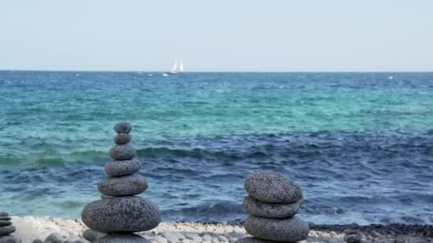 Stone tower on the beach against the azure sea. Beautiful rocks on the background. Peace and tranquility. Clean blue sky. Soul balance. Cobblestone sculptures.