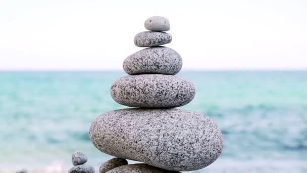 Kamenná věž na pláži proti azurovému moři. Krásné skály na pozadí. Mír a klid. Čistě modré nebe. Rovnováha duše. Dlažební sochy.
