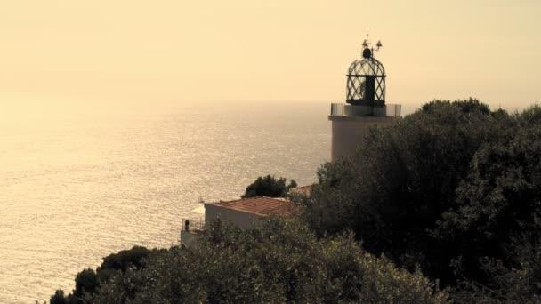 alter Leuchtturm auf einer Kiefernklippe vor dem Hintergrund eines glitzernden Meeres und klaren Himmels. Weg zum Leuchtturm zwischen den Kiefern.