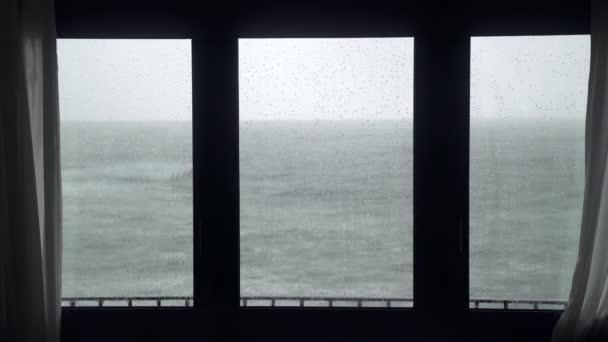 Pohled z okna na bouřlivé moře. Sleduju bouři. Silné zuřící moře. Velké vlny. Větrné deštivé počasí. Pohled na dramatický oceán z okna.
