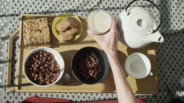 Snídaně na terase. Piknik na slunné terase. Zdravá snídaně. Dívka nalévá mléko do misky s čokoládovými kukuřičnými koulemi. Chutná zdravá snídaně s vločkami, mlékem a sušenkami. Ranní čaj.