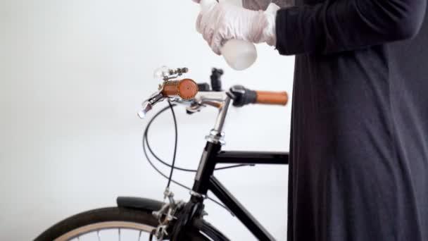 Dezinfekce. Preventivní opatření proti epidemii viru. Karanténa koronaviru. Žena v latexových rukavicích utírá držadla na kole dezinfekcí. Povrchová úprava alkoholem. Zůstaň doma. Ohnisko