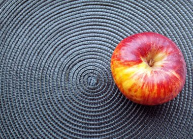 Red apple on a rug. Wicker structure. Dark green background.