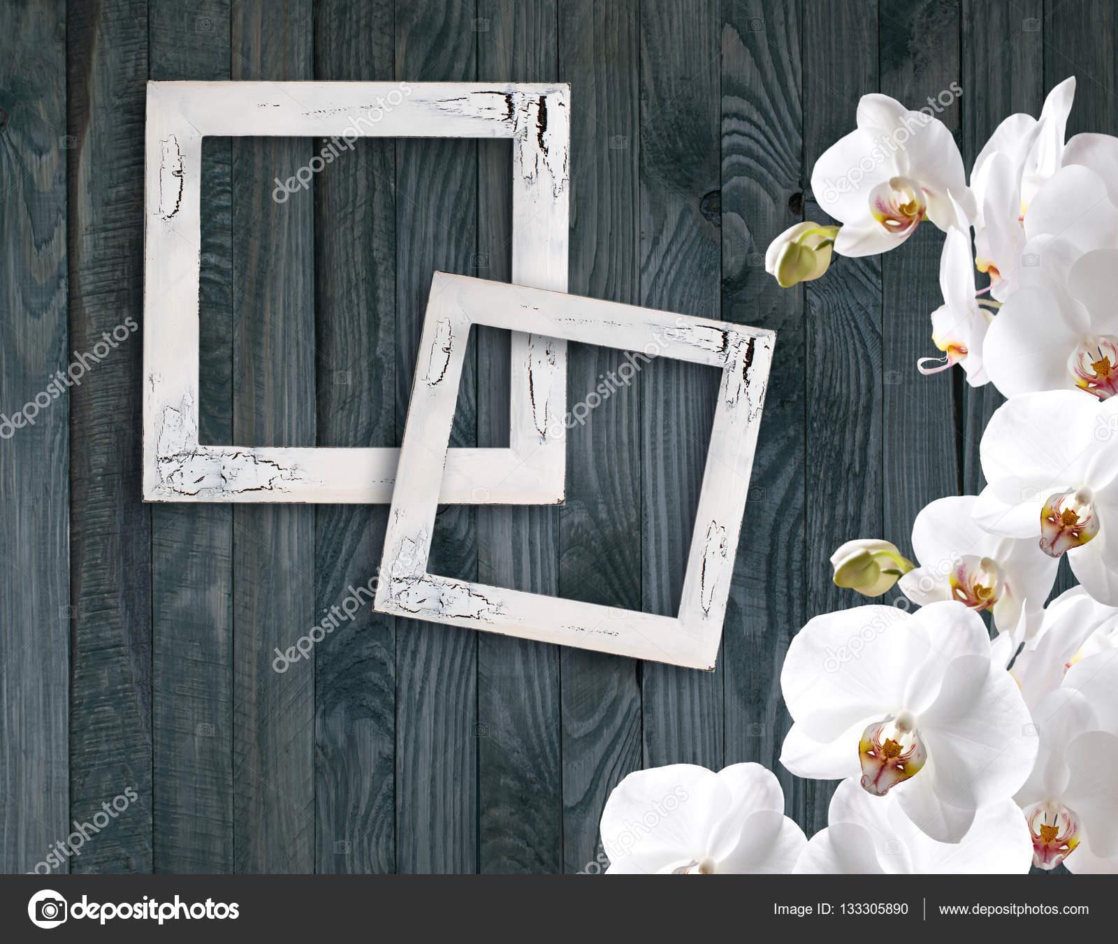 Marco blanco de la orquídea y la foto en fondo de mal plan madera ...
