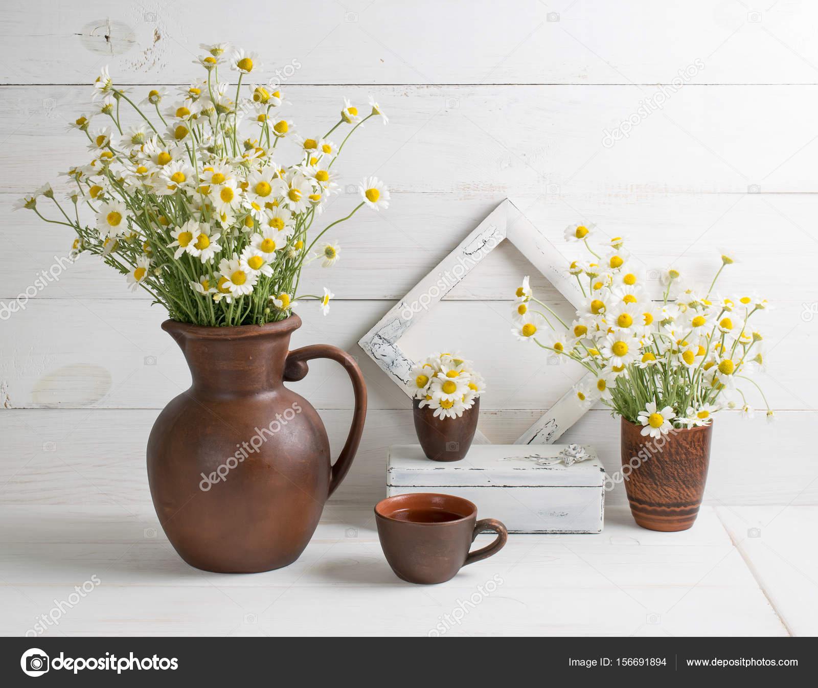 Daisy boeket in kruik van klei met kopje thee en foto frame ...