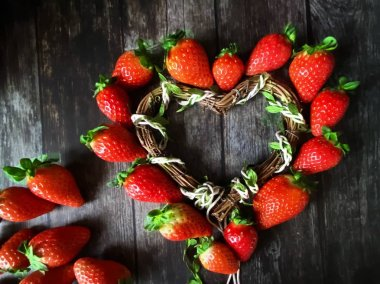 strawberry red  heart-shaped  on wooden background table top wicker basket