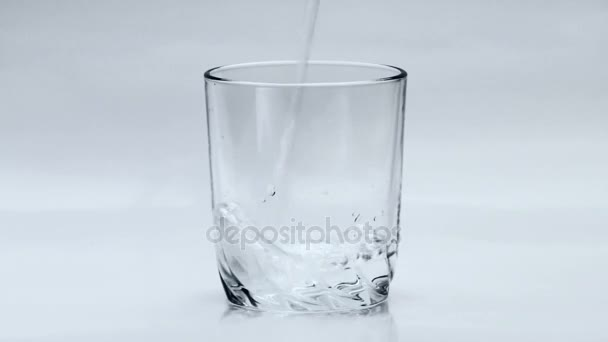 Lít vodu do průhledného skla na bílém pozadí