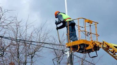 Worker in Cradle of Skylift Colors Lamppost With White Paint