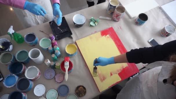 Umělec maluje dřevěnou desku. Červená a žlutá barva. Art Studio. Plechovky a štětce