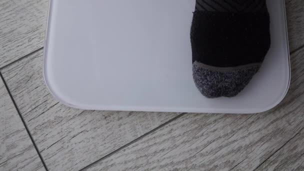 Mužské nohy oblečené v kalhotách a ponožkách jsou na elektronických šupinách. Kontrola tělesné hmotnosti při hubnutí. Každodenní měření hmotnosti, péče o tělo. Zdraví a wellness. 70 kilogramů