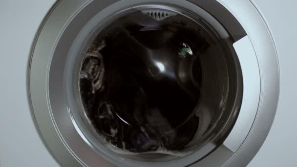 Mosogatás a mosógépben. A mosógép dobjának forgatása közelről.