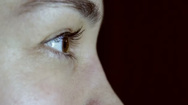 Young beautiful girl opens her green-brown eyes and looks into the distance. Eyes close-up. View from the side.