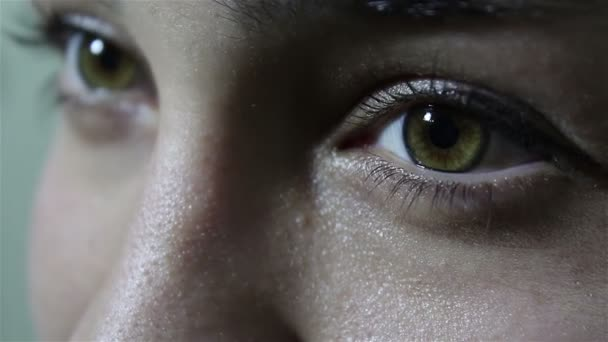 Krásná mladá dívka s velkými žlutohnědými oči vypadá koketně na kameře.