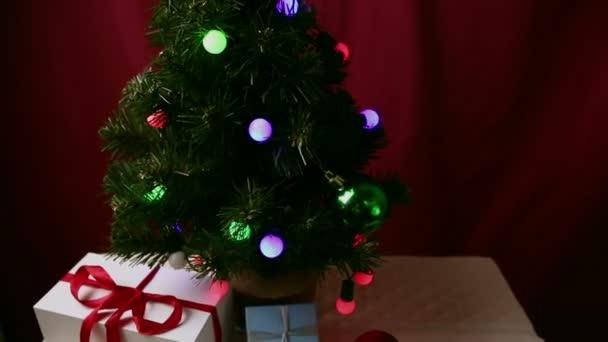 Karácsonyfák színes fényekkel, játékokkal és ajándékokkal. Az újévi ajándékok gyönyörű csomagolásban egy játékokkal és koszorúkkal díszített karácsonyfa alatt vannak..