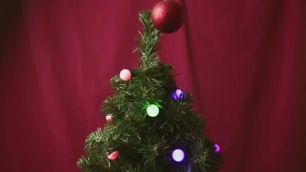 Mužova ruka visí červený lesklý míč na vánoční stromečky.Vánoční stromeček je zdoben gerland a vánoční stromeček hračka.