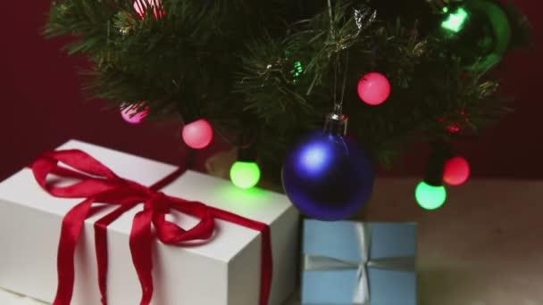 Ruka mladého muže bere malý dárek zpod vánočního stromečku.Dárek na nový rok.