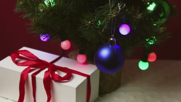 Mužova ruka dává malý dárek do modré krabičky pod vánoční stromeček.Dárek na nový rok pod vánoční stromeček.