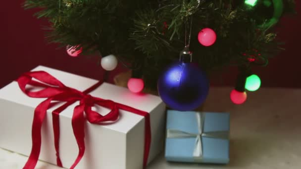 Christmas trees with colorful lights, toys and gifts. New Years gifts in beautiful packaging lie under a Christmas tree decorated with toys and garlands.
