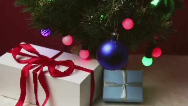 Vánoční stromky s barevnými světly, hračky a dárky. Novoroční dárky v krásném balení leží pod vánočním stromečkem zdobeným hračkami a girlandami.