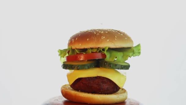 Velký šťavnatý burger s hovězí kotletou, čerstvou zeleninou a roztaveným sýrem.