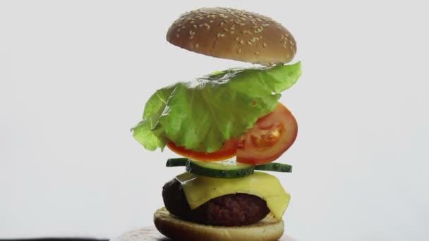 Složení velkého hamburgeru, jednotlivé ingredience visí ve vzduchu. Složené části hamburgru. Fast food, high-calorie food.