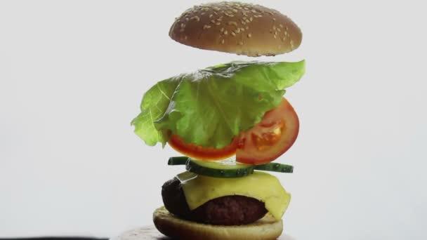 Složené části burgeru. Velký šťavnatý burger s hovězím kotletem, čerstvou zeleninou a smetanovým sýrem. Fast food, high-calorie food.