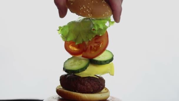 Mužská ruka natahuje hamburger ukazující ingredience.Složení velkého hamburgeru, ingredience jednotlivě visí ve vzduchu. Složené části hamburgru. v