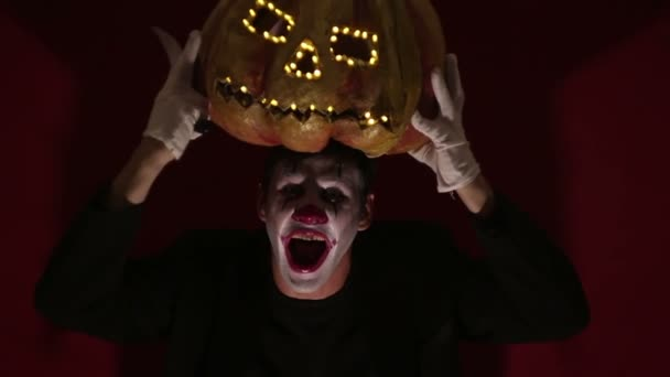 Scary man in the makeup of a clown holds a pumpkin for Halloween and puts it on his head.Terrible clown puts on a mask in the shape of a pumpkin on his head. Terrible clown holds in his hands a Jack-O