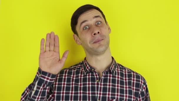 Nahaufnahme Porträt eines jungen attraktiven Kerls, er lächelt und winkt seinen Freunden zum Abschied zu. .Junger gutaussehender Kerl im karierten Hemd, verabschiedet sich und winkt mit der Hand.Porträt auf gelbem Hintergrund.
