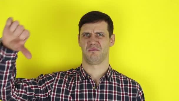 Vtipný fešák ukazuje palec dolů a vyjadřuje svůj nesouhlas. Portrét na žlutém pozadí.
