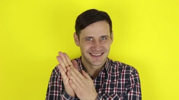Lustiger, hübscher Kerl macht ein schlaues Gesicht und reibt sich die Hände. Porträt eines jungen Mannes, er lächelt verschmitzt und reibt sich die Hände. Porträt auf gelbem Hintergrund.