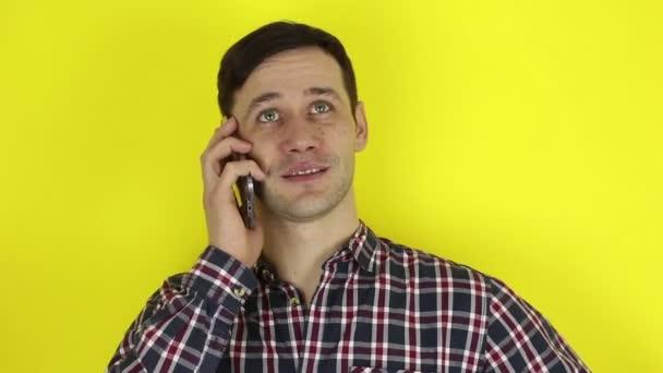 Egy vicces, aranyos srác telefonál az okostelefonján. Egy fiatal fickó portréja. Aktívan beszél egy mobilon. Portré sárga alapon.